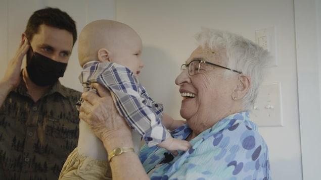 Jacqueline, 91 ans, tiens son arrière-petit-fils dans les bras.